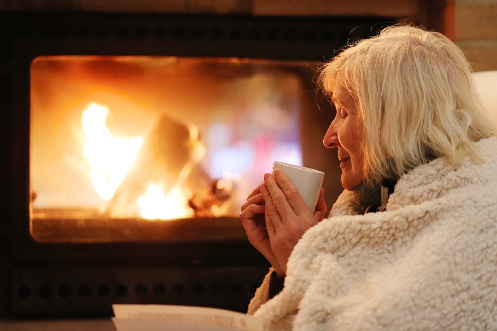 Old lady keeping warm by the fire with a blanket around her and a cup of tea