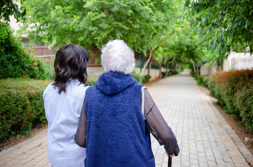 lady with denetia walking outside with her carer