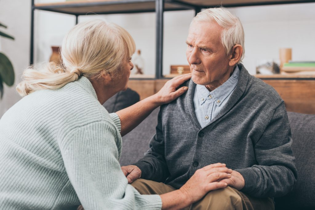 man with dementia sitting down, being comforted by wife